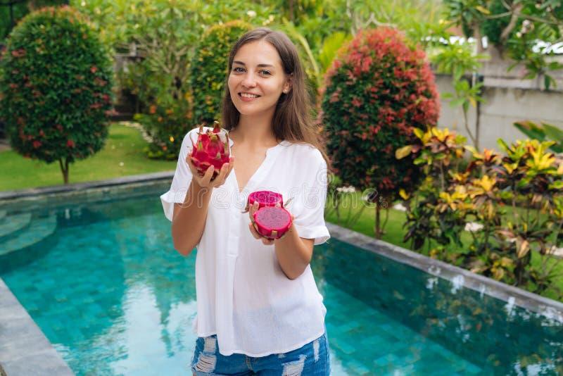 Портрет счастливой девушки держит плоды в ее руках, растительность дракона на предпосылке стоковое изображение