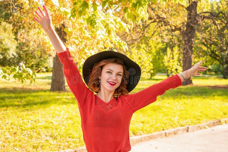 Портрет счастливой женщины в руках шляпы на верхней части в парке осени стоковые фото