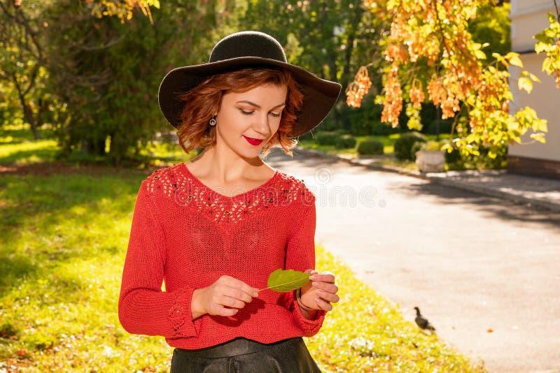 Портрет счастливой женщины в руках шляпы на верхней части в парке осени стоковая фотография rf