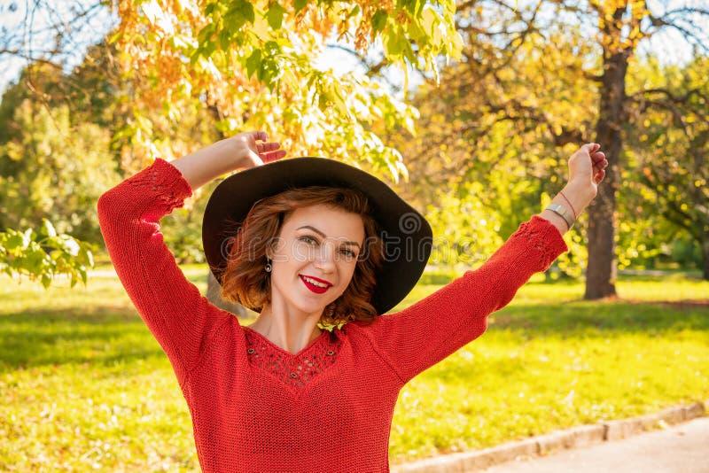 Портрет счастливой женщины в руках шляпы на верхней части в парке осени стоковое фото rf