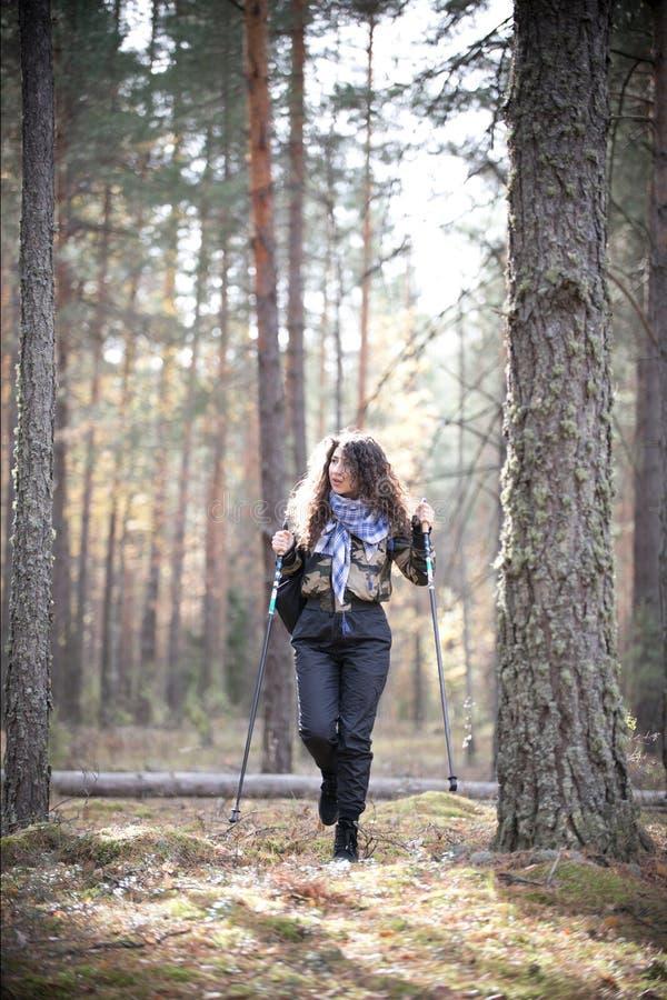 Портрет счастливой женщины с вьющиеся волосы в осени стоя близко к дереву Молодая женщина радостного и улыбок имея потеху внутри стоковая фотография