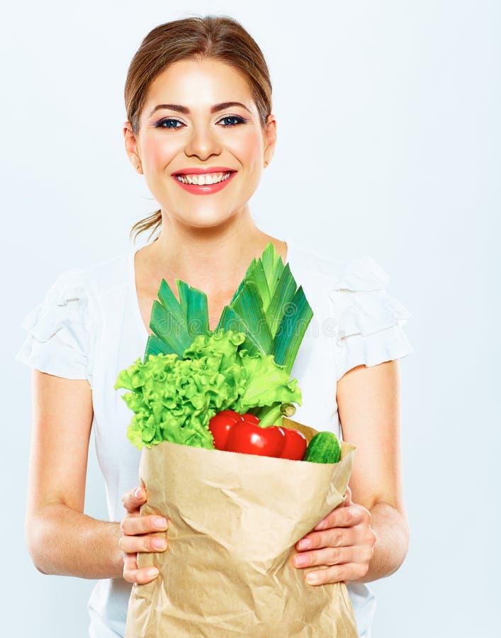 Портрет счастливой женщины с зеленой едой vegan в бумажной сумке стоковые фотографии rf