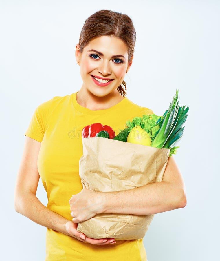 Портрет счастливой женщины с зеленой едой vegan в бумажной сумке стоковое фото rf