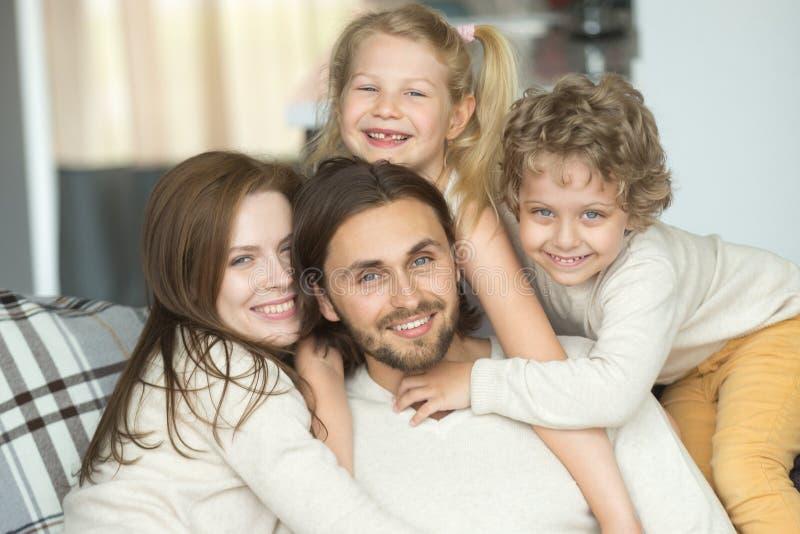 Портрет счастливой жизнерадостной молодой семьи при дети скрепляя togeth стоковая фотография