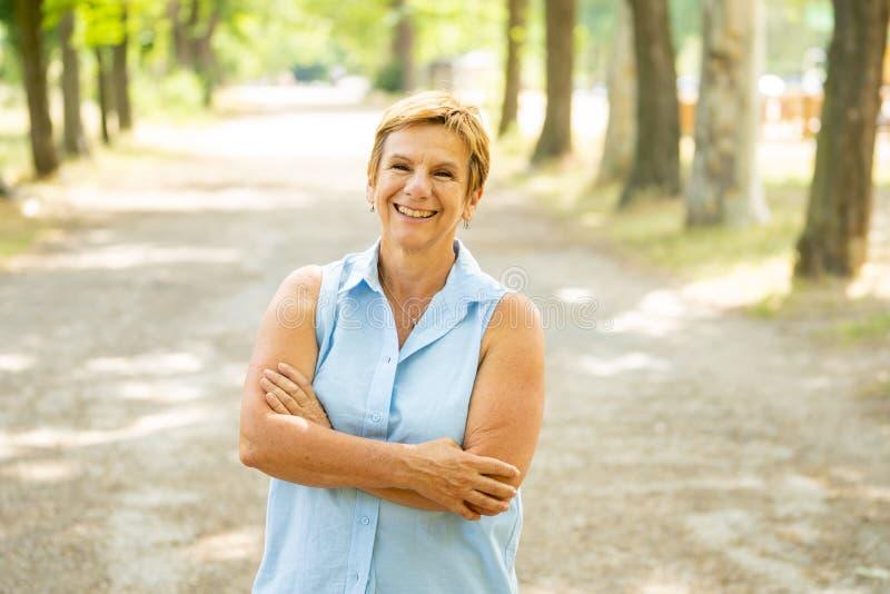 Портрет счастливой зрелой женщины в парке стоковое изображение rf