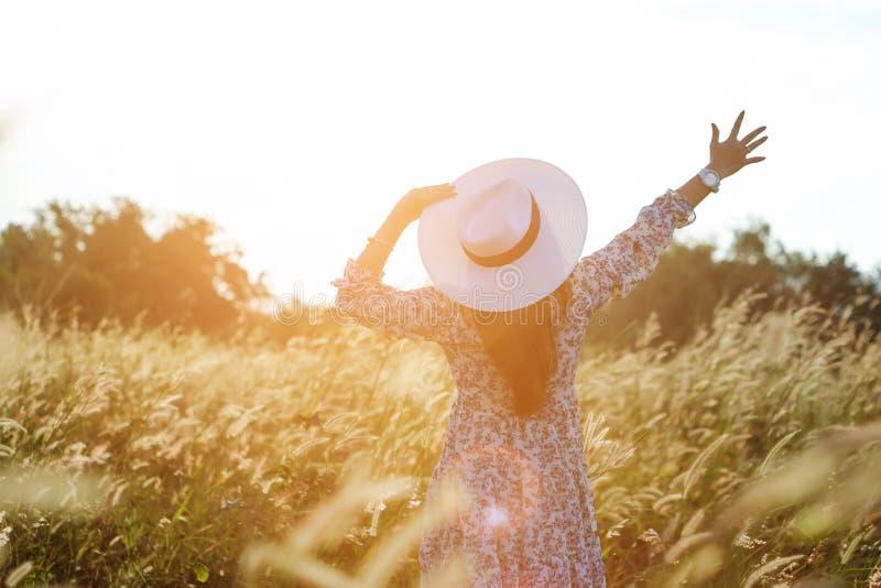 Портрет счастливой и наслаждаясь молодой женщины на луге на солнечный летний день Жизнерадостная девушка на заходе солнца Образ ж стоковые фото