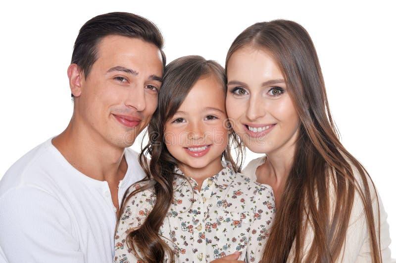 Портрет счастливой красивой семьи из трех человек представляя на белой предпосылке стоковые изображения rf