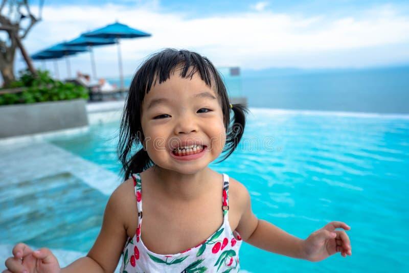 Портрет счастливой маленькой азиатской девушки играя на море, милый усмехаться стоковое фото rf