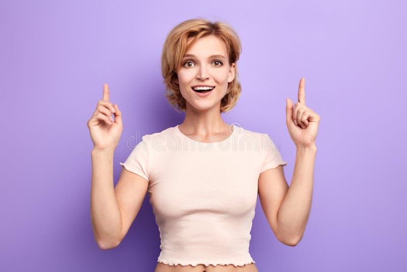 Портрет счастливой маленькой девочки одел случайно указывать пальцы вверх стоковое фото rf