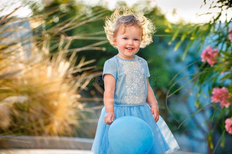 Портрет счастливой маленькой девочки с курчавыми светлыми волосами в случайных одеждах представляя outdoors с голубыми баллонами стоковое фото rf