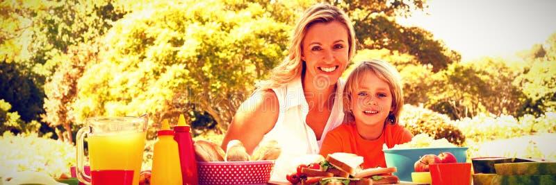 Портрет счастливой матери и сына имея еду в парке стоковое фото rf