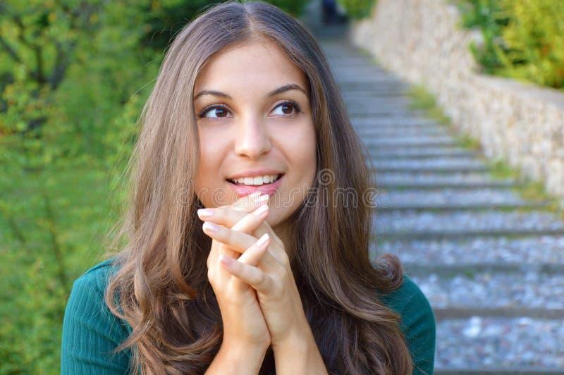 Портрет счастливой многообещающе показывать усмехаясь молодой женщины в вскользь умной зеленой одежде стоковое фото