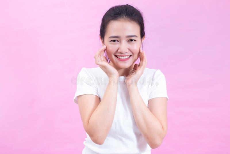 Портрет счастливой молодой азиатской женщины изолированной на розовой предпосылке Сторона красоты с естественной кожей стоковое изображение rf