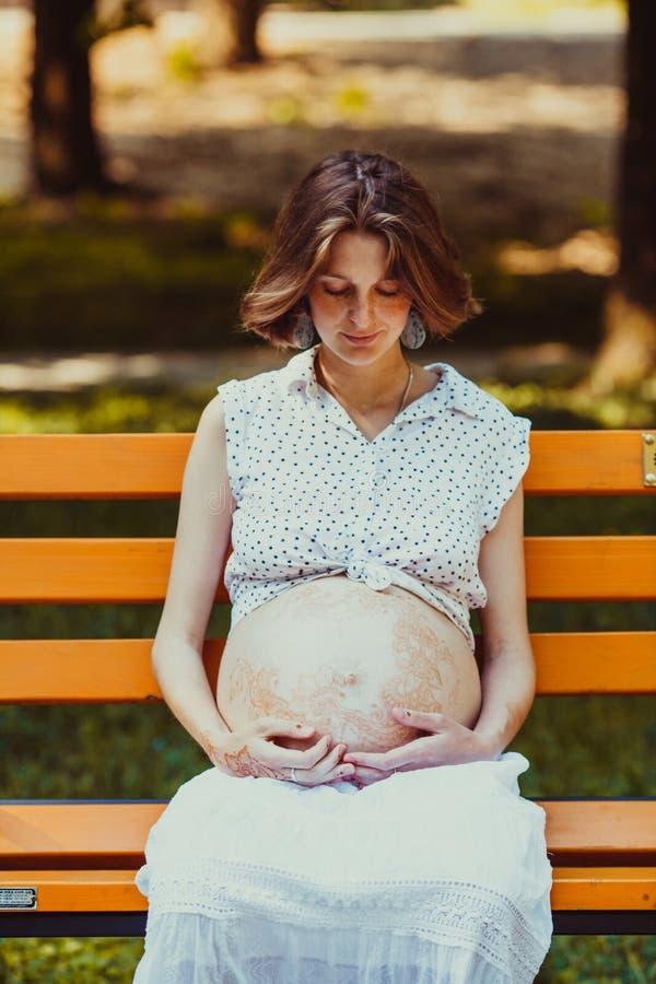 Портрет счастливой молодой беременной дамы сидя на стенде стоковые фото