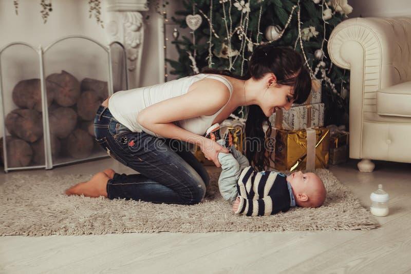 Портрет счастливой молодой матери при ребенок околпачивая вокруг около рождественской елки и камина Женщина держит ноги ` s младе стоковые изображения