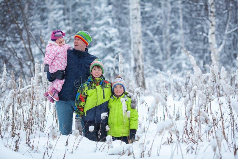 Портрет счастливой семьи в парке зимы Отец, сын и маленький смеяться над дочери стоковое фото rf