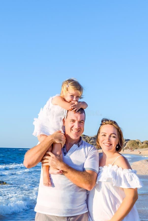 Портрет счастливой семьи из трех человек - беременная мать, отец и дочь смотря камеру и идя на пляж Vacati семьи стоковое изображение rf