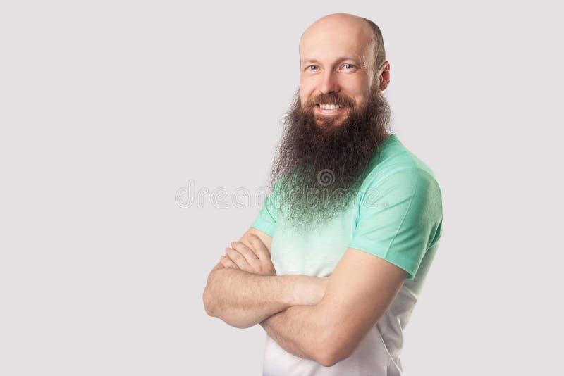 Портрет счастливой удовлетворенной середины постарел лысый человек с длинной бородой в зеленом положении футболки с пересеченными стоковое изображение rf
