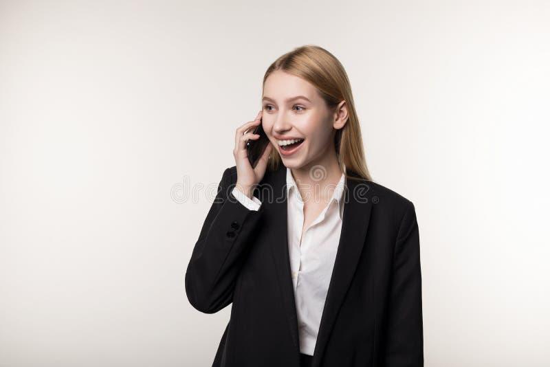 Портрет счастливой усмехаясь коммерсантки одетой в черном телефоне пользы костюма стоковое фото rf