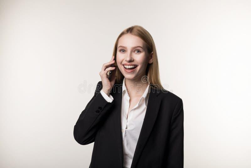 Портрет счастливой усмехаясь коммерсантки одетой в черном телефоне пользы костюма стоковые фотографии rf