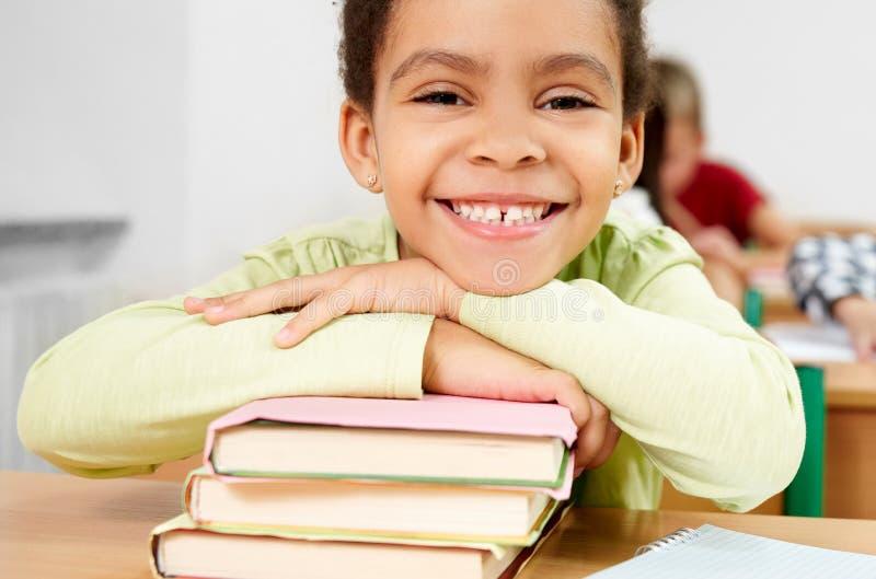 Портрет счастливой школьницы в классе начальной школы стоковые фото