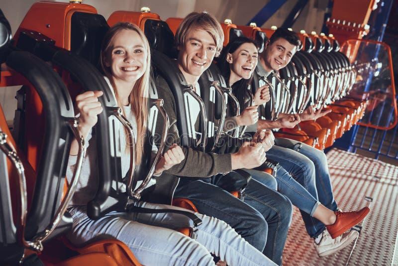 Портрет счастливых друзей наслаждаясь на carousel стоковая фотография rf