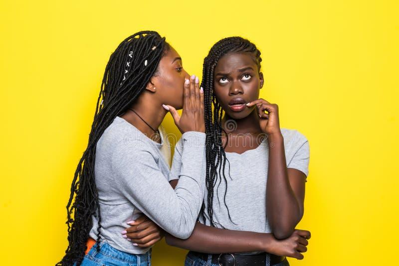 Портрет 2 счастливых молодых африканских женщин деля секреты изолированный над желтой предпосылкой стоковые изображения rf