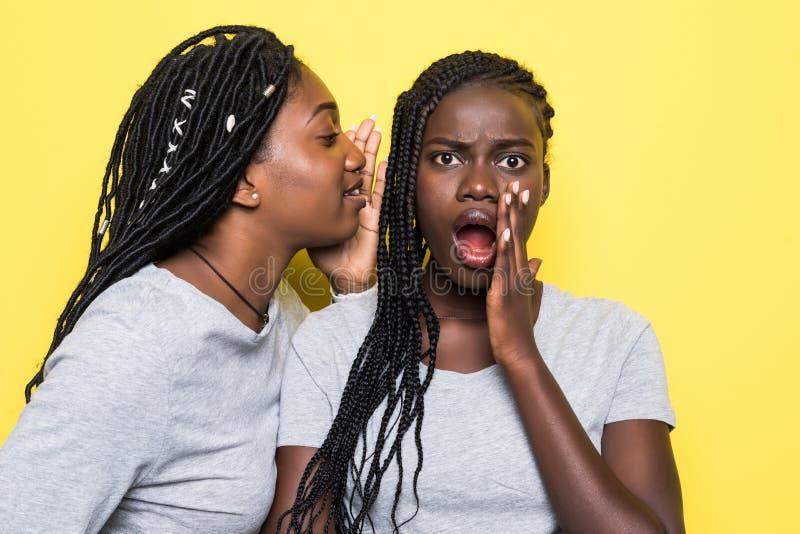 Портрет 2 счастливых молодых африканских женщин деля секреты изолированный над желтой предпосылкой стоковая фотография rf