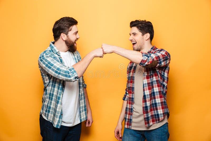 Портрет 2 счастливых молодых человеков давая кулак bump стоковые изображения rf
