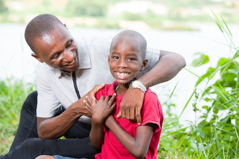 Портрет счастливых отца и сына в парке стоковая фотография rf