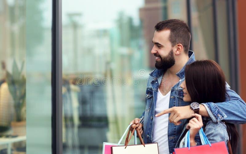 Портрет счастливых пар с хозяйственными сумками после ходить по магазинам в городе стоковые фотографии rf