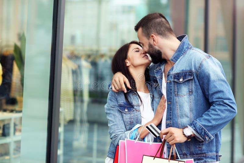 Портрет счастливых пар с хозяйственными сумками после ходить по магазинам в городе стоковая фотография rf