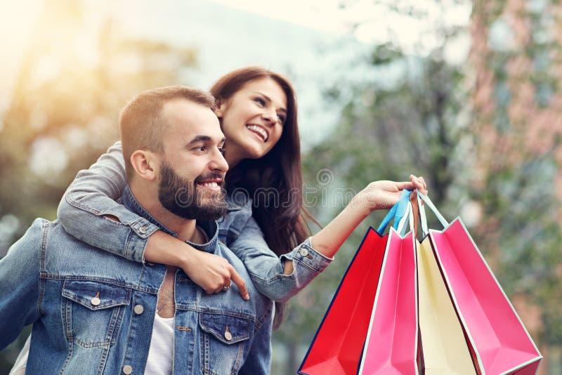 Портрет счастливых пар с хозяйственными сумками после ходить по магазинам в городе стоковое фото rf