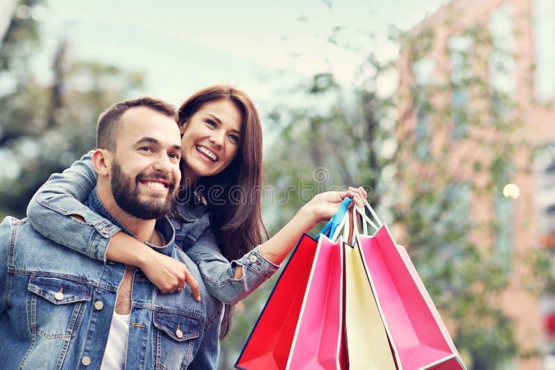 Портрет счастливых пар с хозяйственными сумками после ходить по магазинам в городе стоковое изображение rf