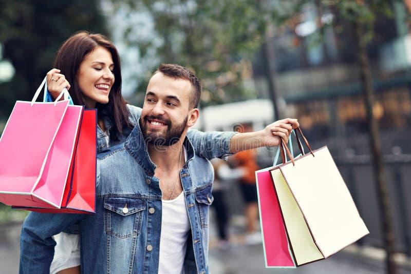Портрет счастливых пар с хозяйственными сумками после ходить по магазинам в городе стоковые изображения rf