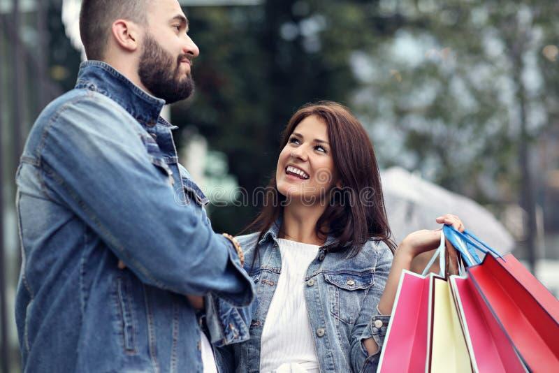 Портрет счастливых пар с хозяйственными сумками после ходить по магазинам в городе стоковая фотография
