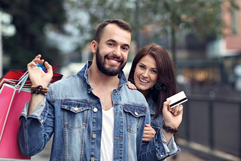 Портрет счастливых пар с хозяйственными сумками после ходить по магазинам в городе стоковое изображение