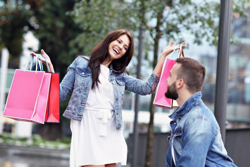 Портрет счастливых пар с хозяйственными сумками после ходить по магазинам в городе стоковое фото