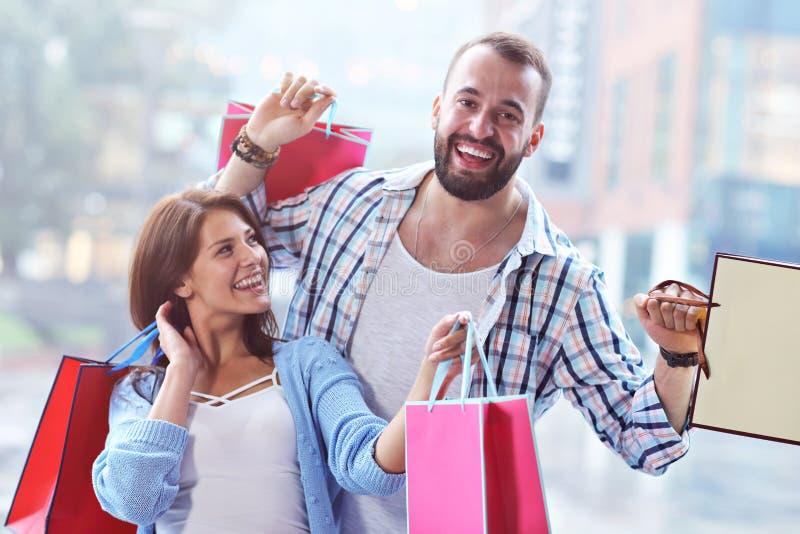 Портрет счастливых пар с хозяйственными сумками после ходить по магазинам в городе стоковые изображения