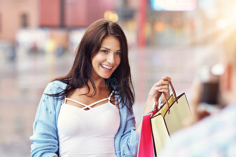 Портрет счастливых пар с хозяйственными сумками после ходить по магазинам в городе стоковые фото