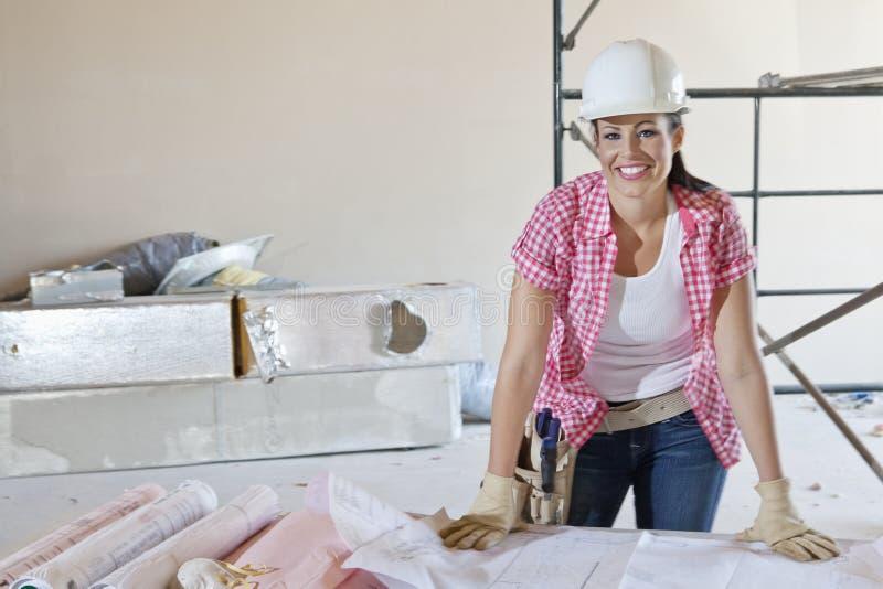 Портрет счастливого архитектора женщины с зданием планирует стоковое фото
