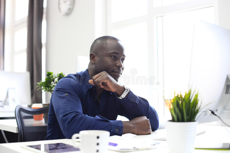Портрет счастливого Афро-американского предпринимателя показывая компьютер в офисе стоковые фотографии rf