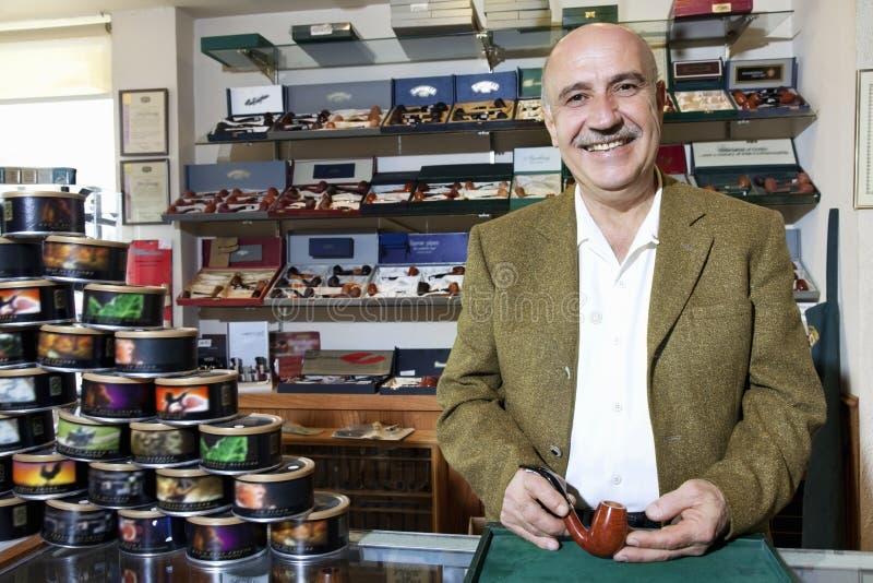 Портрет счастливого зрелого владельца магазина табака с чонсервными банками на дисплее стоковая фотография