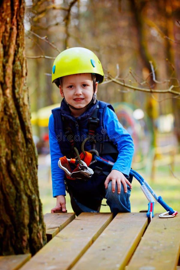 Портрет счастливого мальчика имея потеху в парке приключения усмехаясь к шлему и оборудованию для обеспечения безопасности камеры стоковое фото