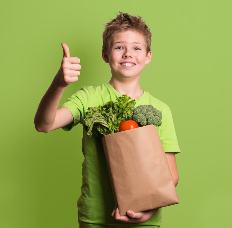 Портрет счастливого мальчика показывая большие пальцы руки вверх показывать, изолированный над g стоковое изображение rf