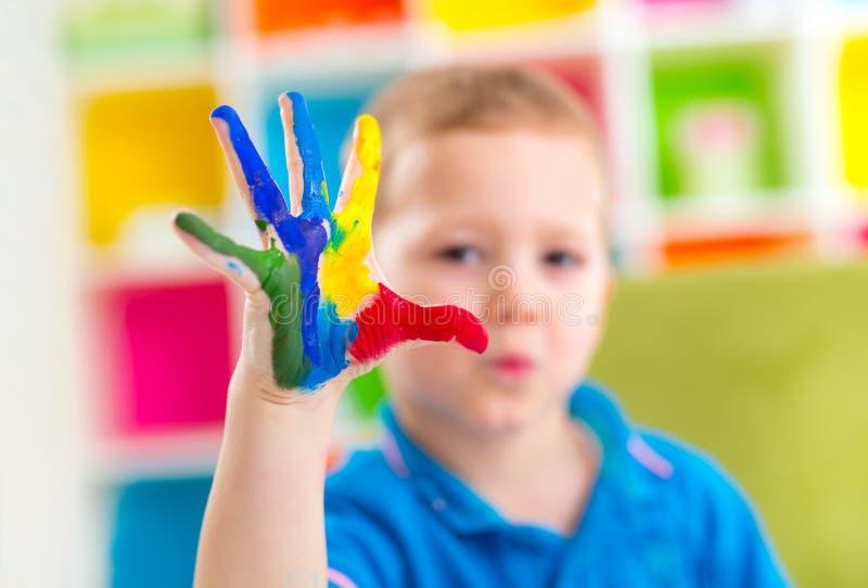 Портрет счастливого мальчика с красочными покрашенными руками стоковые изображения