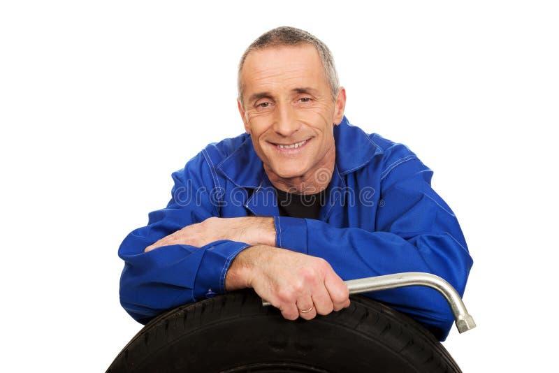 Портрет счастливого механика с автошиной и ключем стоковая фотография rf