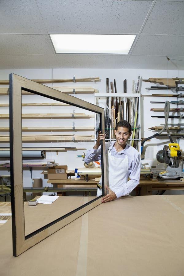 Портрет счастливого молодого человека работая на большой картинной рамке в мастерской стоковое фото