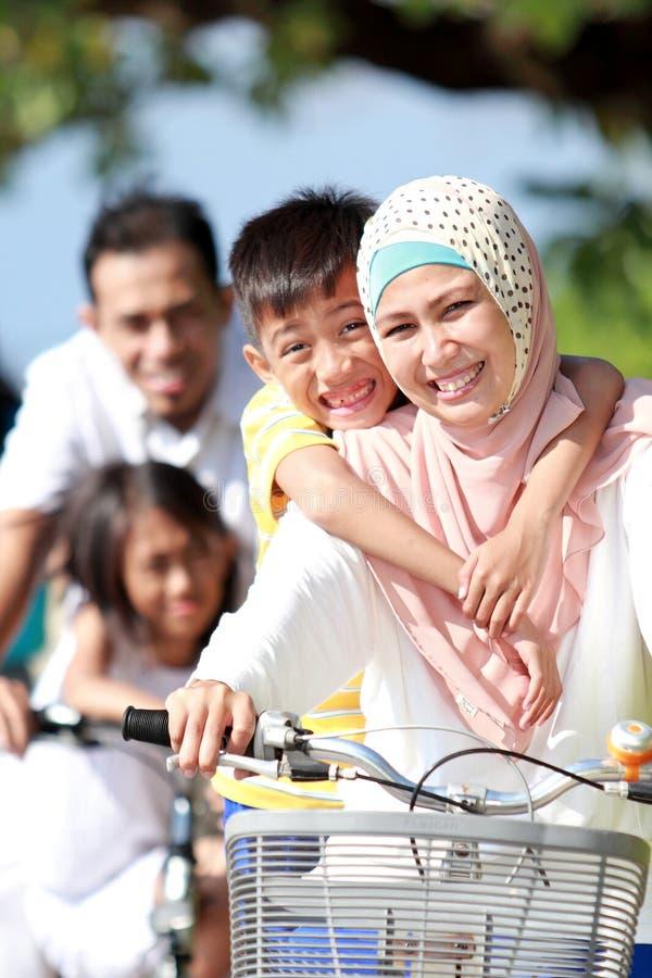 Портрет счастливого мусульманского катания семьи велосипед совместно стоковое изображение rf