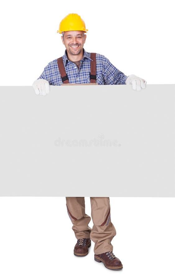 Портрет счастливого подрядчика проводя плакат стоковая фотография